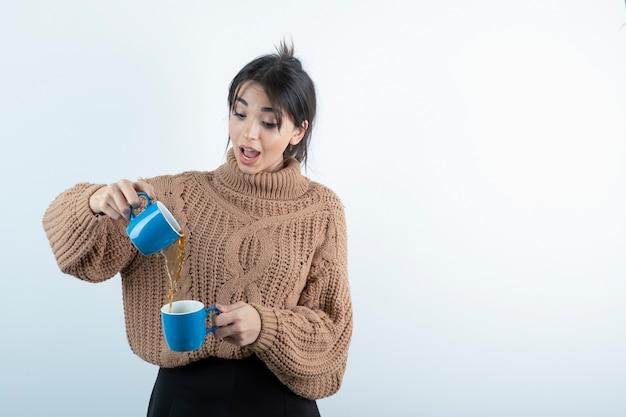 白い壁にお茶を注ぐ若い女性の肖像画