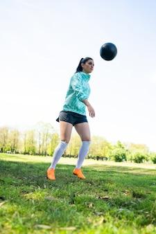 サッカーのスキルを練習し、サッカーボールでトリックを行う若い女性の肖像画。ボールをジャグリングするサッカー選手。スポーツのコンセプト。