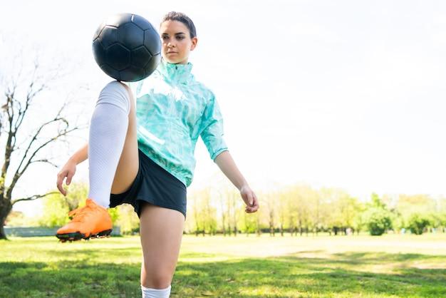 축구 기술을 연습 하 고 축구 공을 트릭을 하 고 젊은 여자의 초상화. 공을 저글링하는 축구 선수. 스포츠 개념.