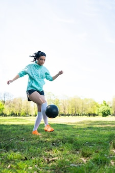 サッカーのスキルを練習し、サッカーボールでトリックを行う若い女性の肖像画。ボールをジャグリングするサッカー選手。スポーツの概念。