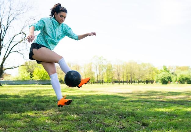 サッカーのスキルを練習し、サッカーボールでトリックを行う若い女性の肖像画。ボールをジャグリングするサッカー選手。