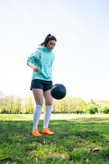 Портрет молодой женщины, практикующей футбол и выполняющей трюки с футбольным мячом
