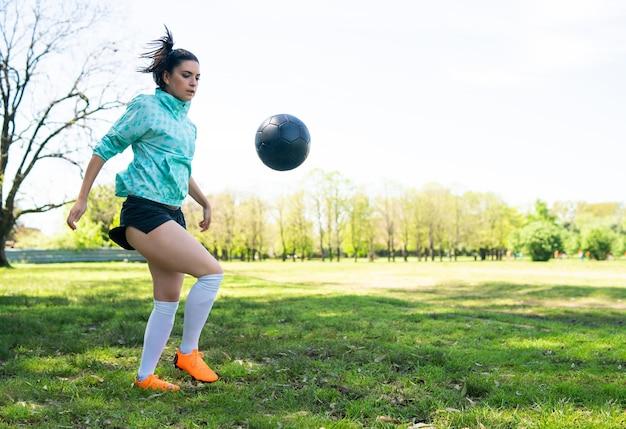 サッカーのスキルを練習し、サッカーボールでトリックを行う若い女性の肖像画