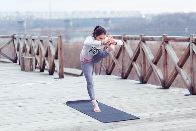 自然の中で屋外でヨガのポーズを練習している若い女性の肖像画美しい少女はアーサナを練習します