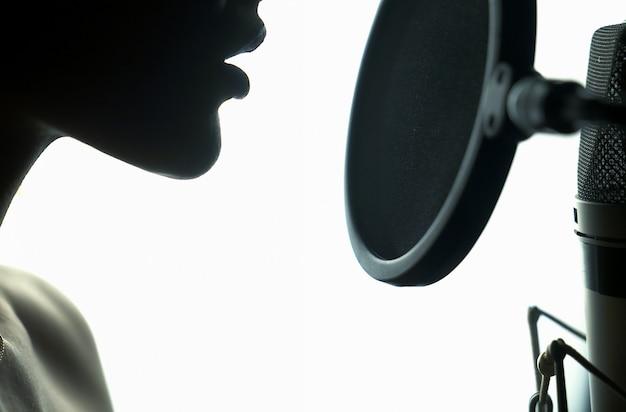 전문 스튜디오에서 노래를 녹음하는 젊은 여자의 초상화.
