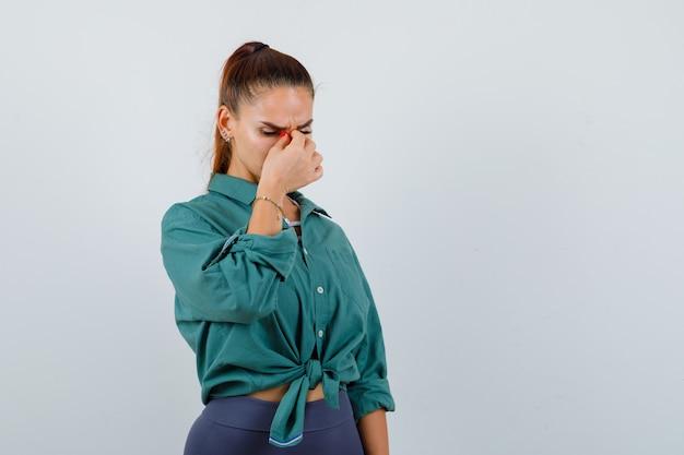 Портрет молодой женщины, протирающей глаза и нос в зеленой рубашке и выглядящей усталой, вид спереди