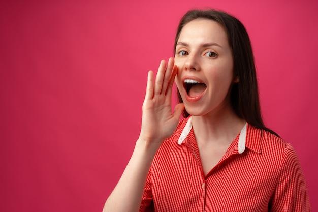 Портрет молодой женщины, кричащей на розовом фоне