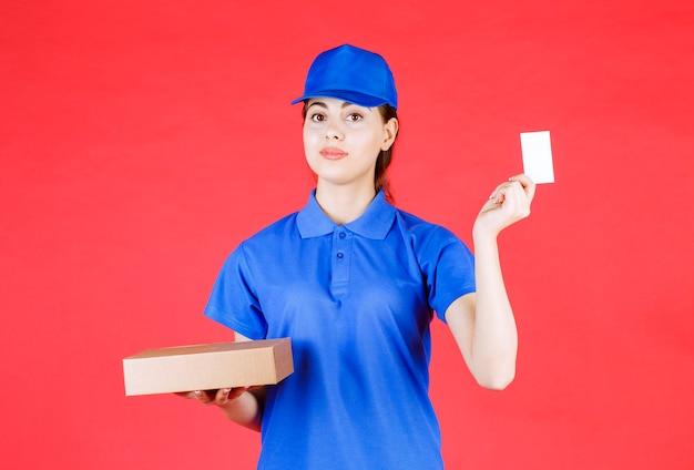 명함을 보여주고 판지 상자를 들고 있는 젊은 여성의 초상화.
