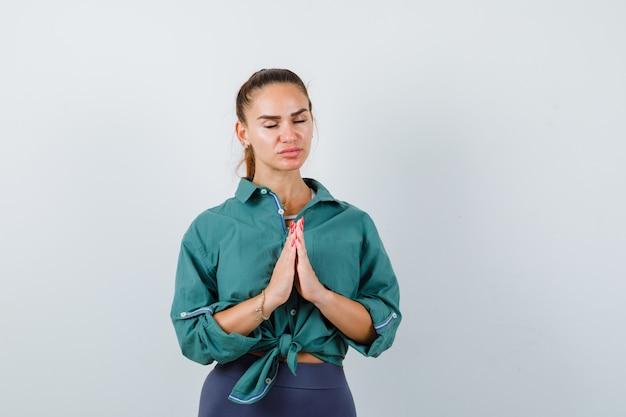Портрет молодой женщины, показывающей жест намасте в зеленой рубашке и выглядящей обнадеживающей, вид спереди