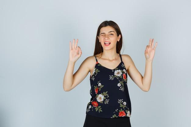 Портрет молодой женщины, показывающей жест ок, моргая в блузке и глядя на веселый вид спереди