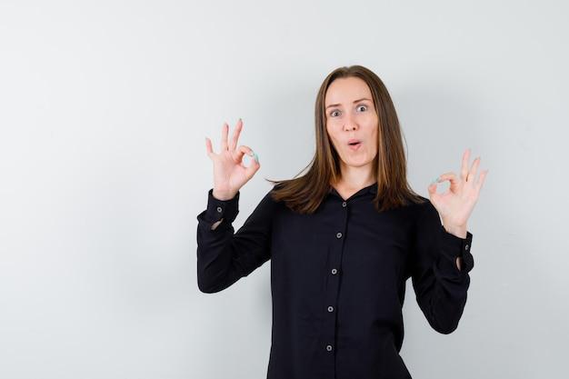Портрет молодой женщины, показывающей жест ок