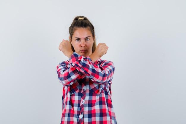 Портрет молодой женщины, показывающей жест стоп со скрещенными кулаками в повседневной рубашке и серьезной вид спереди