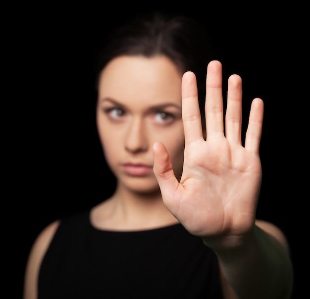 手で停止ジェスチャーを示す若い女性の肖像画
