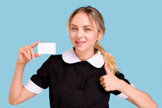 Портрет молодой женщины, показывая большой палец вверх жест, удерживая белый пустой визитная карточка против голубой стене