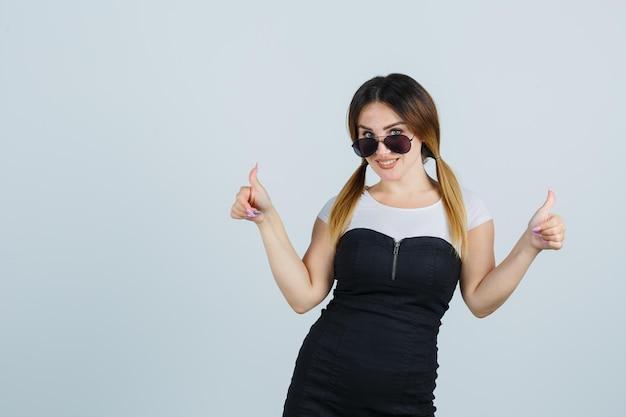 Портрет молодой женщины показывает палец вверх