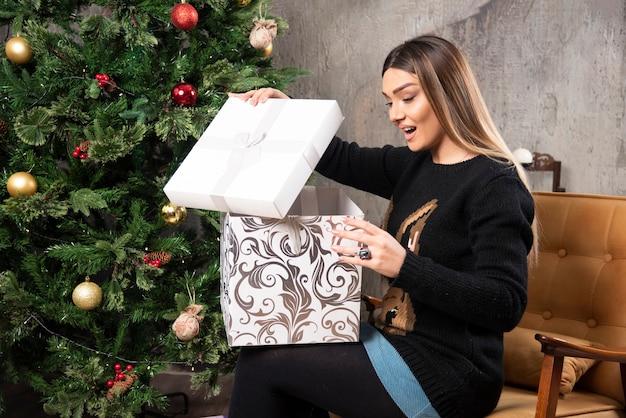 クリスマスプレゼントに座って見ている若い女性の肖像画。高品質の写真