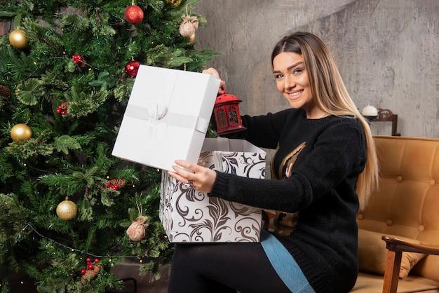 앉아서 크리스마스 선물을 여는 젊은 여자의 초상화. 고품질 사진