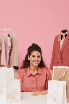 紙袋のテーブルに座って、背景のラックに服を着て笑っている若い女性の肖像画