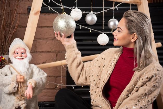 젊은 여자가 바닥에 앉아 크리스마스 공을 들고의 초상화 .high 품질 photo