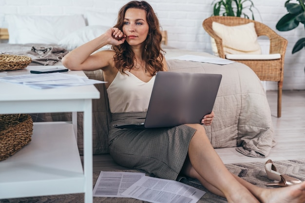 ノートパソコンで床に座って、目をそらしている若い女性の肖像画。