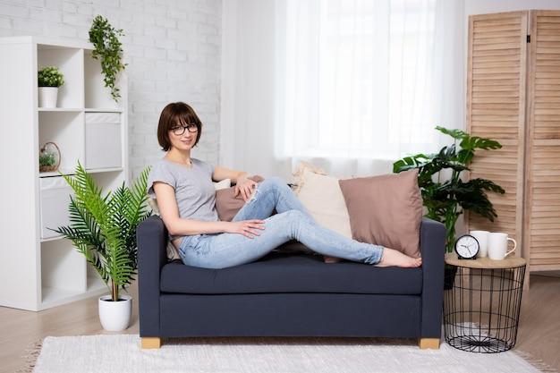 リビングルームのソファに座っている若い女性の肖像画