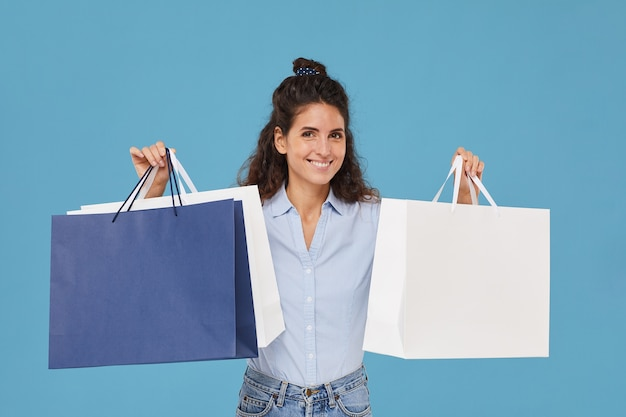 彼女は買い物中毒である紙の買い物袋を笑顔で持っている若い女性の肖像画