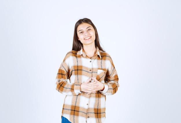 Портрет молодой женщины, счастливо улыбаясь на белой стене.