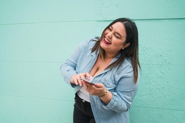 屋外で彼女の携帯電話でテキストメッセージを入力しながら笑っている若い女性の肖像画