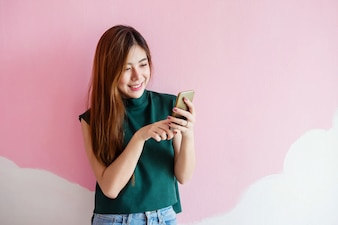 Portrait of Young Woman Smiling while using Smart Phone at the wall