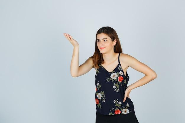 ブラウス、スカート、陽気な正面図で無知なジェスチャーで手のひらを広げている若い女性の肖像画
