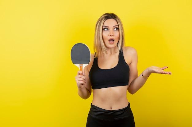 노란색 벽에 탁구 라켓을 들고 서 있는 젊은 여성의 초상화.