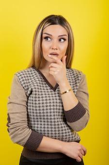 서서 노란색을 바라보는 젊은 여성의 초상화.
