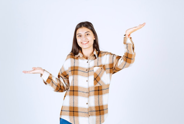Портрет молодой женщины, стоящей и позирующей на белой стене.