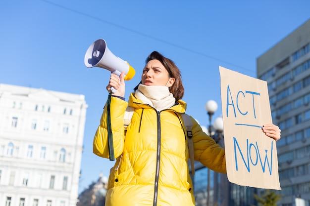 町の屋外に立って、テーブルactnowを示している若い女性の肖像画。パンデミック、政治、または環境問題に抗議する女性のデモ委員会。単一の抗議。
