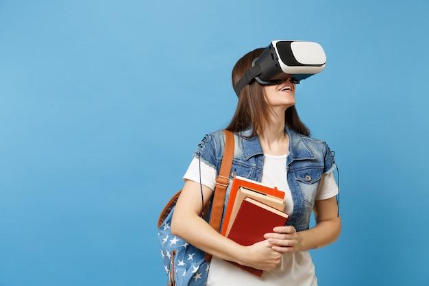 Портрет студента молодой женщины в джинсовой одежде с рюкзаком в очках виртуальной реальности, глядя вверх, держа школьные учебники, изолированные на синем фоне. обучение в средней школе университетского колледжа.