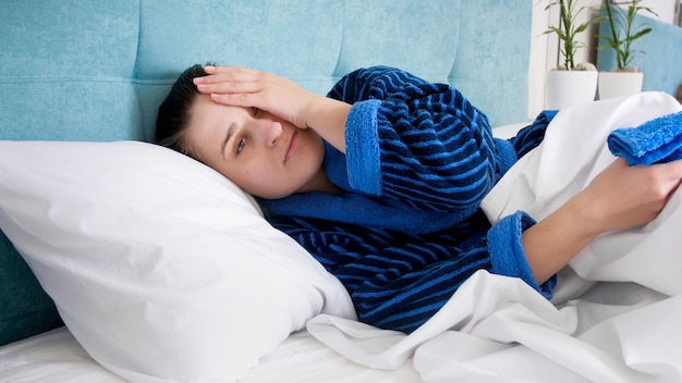 침대에 누워 편두통 두통으로 고통받는 젊은 여자의 초상화.