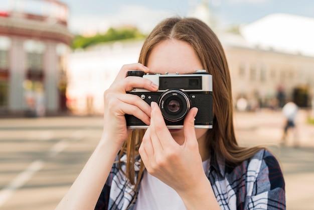 카메라와 함께 사진을 복용하는 젊은 여자의 초상화
