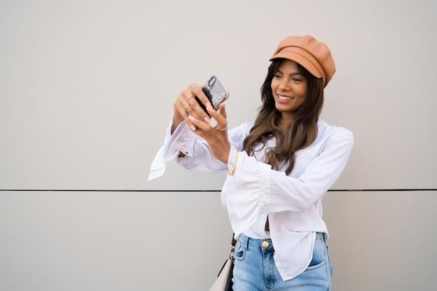 屋外に立っている間彼女のmophile電話でselfiesを取る若い女性の肖像画。アーバンコンセプト。