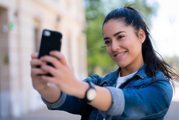 야외에서 서있는 동안 그녀의 mophile 전화로 셀카를 복용하는 젊은 여자의 초상화