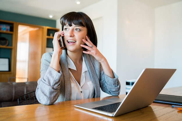 Портрет молодой женщины разговаривает по мобильному телефону и работает дома с ноутбуком. концепция домашнего офиса. новый нормальный образ жизни.