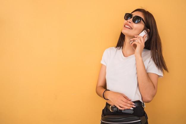 黄色の壁に対して電話で話している若い女性の肖像画。都市とコミュニケーションの概念。