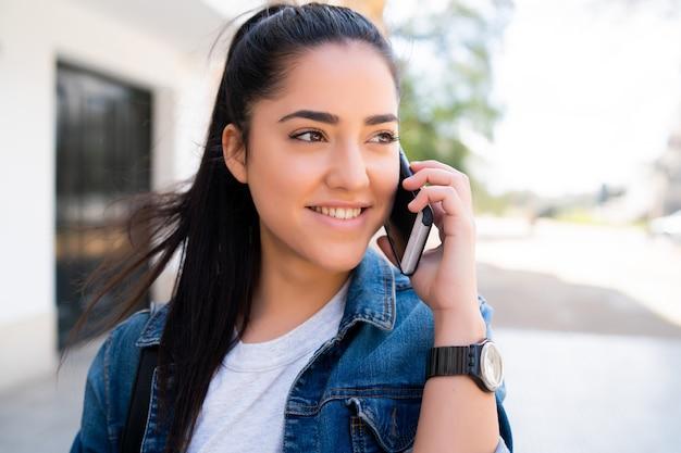 通りで屋外に立っている間、電話で話している若い女性の肖像画。都市とコミュニケーションの概念。