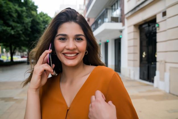 通りを屋外で歩きながら電話で話している若い女性の肖像画。都市とコミュニケーションの概念。