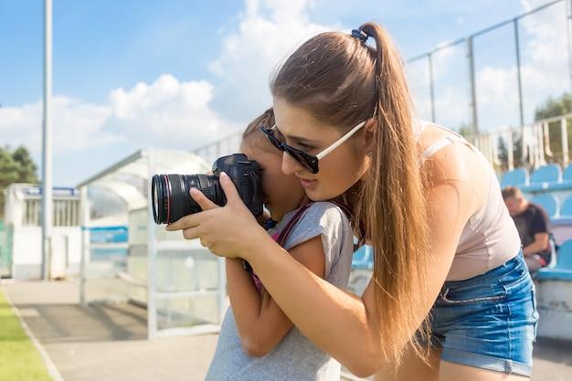 Портрет молодой женщины, которая учит маленькую девочку фотографировать с помощью профессиональной камеры