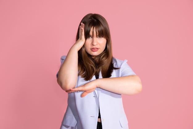생각하고, 피곤하고 지루해 보이는 젊은 여성의 초상화는 팔 근처에 있는 우울증 문제, 스튜디오 촬영, 분홍색 배경입니다.