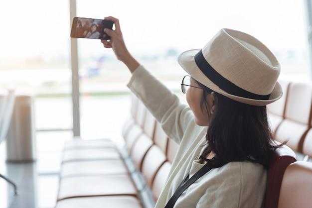 스마트 폰으로 selfie를 복용하는 젊은 여자 여행자 착용 안경 및 모자의 초상화. 행복 하 게 웃는 여자 승객. 여행, 휴가 메이커.