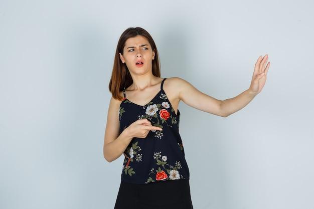 ブラウス、スカートを脇に向け、怖い正面図を見て、手で自分自身をブロックしようとしている若い女性の肖像画