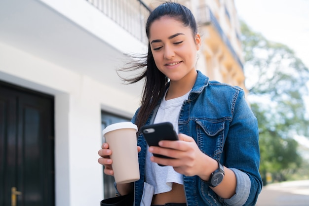 Портрет молодой женщины, печатающей по телефону и держащей чашку кофе, стоя на открытом воздухе на улице