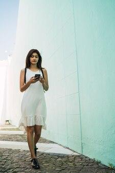 通りで屋外で彼女の携帯電話を使用して若い女性の肖像画