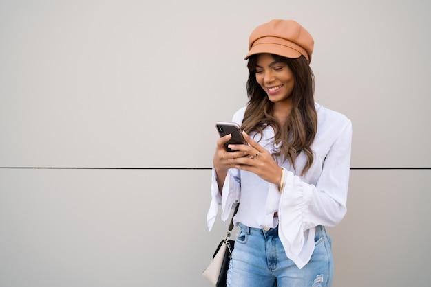 거리에 야외에서 서있는 동안 그녀의 휴대 전화를 사용하는 젊은 여자의 초상화